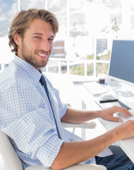 Smiling designer working at his desk in modern office-1-1